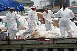 06 June 2010. Barataria Bay to Grand Isle, Jefferson/Lafourche Parish, Louisiana. <br /> Oil clean up workers in full hazmat suits clear away oil soaked boom that has been delivered to the staging area on Grand Isle. The ecological and economic impact of BP's oil spill is devastating to the region. Oil from the Deepwater Horizon catastrophe is evading booms laid out to stop it thanks in part to the dispersants which means the oil travels at every depth of the Gulf and washes ashore wherever the current carries it. The Louisiana wetlands produce over 30% of America's seafood and are the most fertile of their kind in the world.<br /> Photo; Charlie Varley/varleypix.com