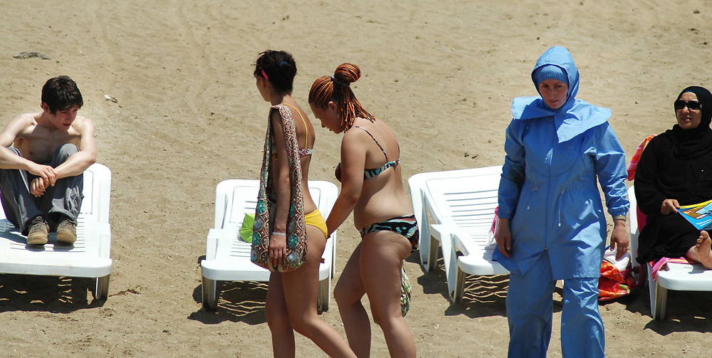 Women in bikinis stroll past fellow tourists in burkinis - also known as hasemas - on the beach at Alanya on the gulf  of Antalya, Turkey.  The upmarket Bera Alanya hotel in the resort is aimed at conservative middle class Muslims who prefer women to cover up in public.  The Turkish constitution prevents women covering their heads in official buildings - including universities - but the right-wing, religiously conservative AK party is keen to overturn this law.  The party has repeatedly clashed with the country's military leaders who regard themselves as protectors of the secular constitution.