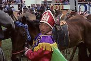 Mongolia. Ulaanbaatar. A yurt transformed in a monastery Oulan Bator   / Yourte transformée en temple. OULAN BATOR, Mongolie.Offrandes sur un autel dans une yourte transformée en temple. Près du grand monastère de GANDANTEGTCHINLIN une yourte est aménagée en temple. Au fond, Statuettes et tankas de divinités bouddhiques forment un panthéon devant lequel on a dressé une table recouverte de tissu rouge. On y a déposé des petites lampes à beurre, des coupelles remplies de farine d'orge pétrie de beurre. Certaines sont surmontées de petits morceaux triangulaires de fromages, d'autres de graines de blé avec bâtonnet d'encens. Toutes ces offrandes sont disposées symétriquement dans une figure de losange. Au bord de la table, à droite, un brûle-encens, une coupelle de gâteau de semoule et deux coupelles de lait dont l'une s'est renversée. (OULAN BATOR,) /   /  43       P0002560