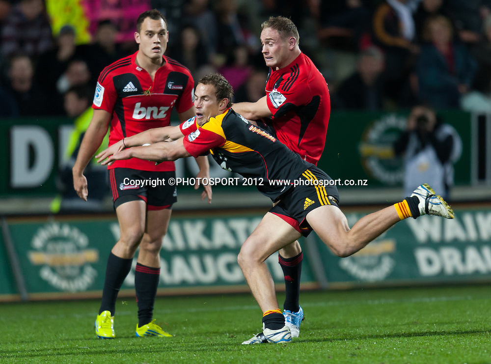 Chiefs' Andrew Horrell attempts to block a kick by Crusaders' Andy Ellis with Israel Dagg looking on during the Super Rugby Semi Final won by the Chiefs (20-17) against the Crusaders at Waikato Stadium, Hamilton, New Zealand, Friday 27 July 2012. Photo: Stephen Barker/Photosport.co.nz