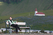 Young woman relaxing on bench, church in background. Vik. Iceland.
