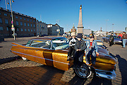 During summer from June to Septemper, every first Friday of the month is Vintage Car Cruising Night. Hundreds of classic American cars cruise around downtown Helsinki and meet at special places to have a good time, here at Kauppatori (Market Square), Uspenski orthodox cathedral in background. 1959 Cadillac DeVille sedan. Kids of the owner posing on top of the car for a souvenir photo.