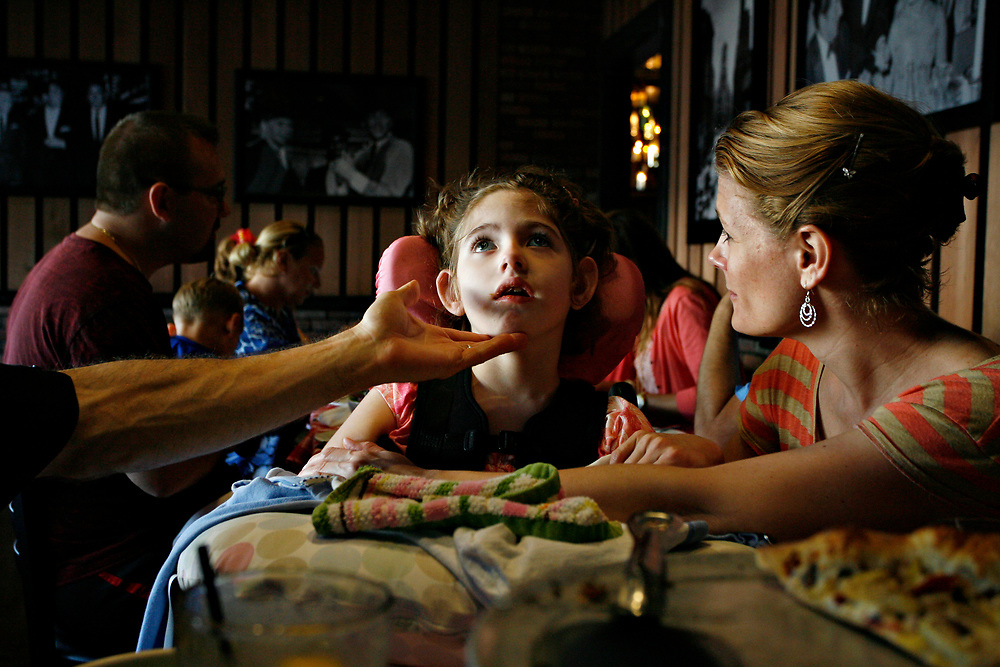 MELISSA LYTTLE   |   Times<br /> SP_351237_LYTT_TWINS_19 (March 30, 2012, Clearwater, Fla.) Jon Scheinman reaches out to comfort Olivia, while Allison looks on with concern, after noticing Olivia's chin quivering and the onset a small seizure during dinner at one of their favorite pizza places. It's a huge undertaking to go out as a family, but they've found places near their house that they're comfortable in and have become regulars at. [MELISSA LYTTLE, Times]