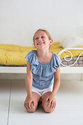 Young Girl Kneeling on Bedroom Floor Smiling