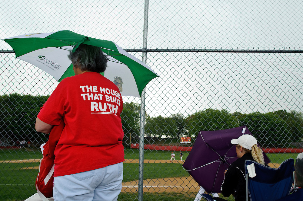 "(photo by Matt Roth).Friday, April 16, 2010.Assignment ID: 30095633A..Fina DiVincenzo, left, wears a Cardinal Gibbons shirt that says ""The House That Build Ruth,"" celebrating Babe Ruth's beginnings at the St. Mary's Industrial School, which is now Gibbons. DiVincenzo and Jeanette Ambrose, right, both have seniors on the team, and keep watching ghe game despite the rain. ..The Archdiocese of Baltimore announced thirteen Catholic Schools will close at the school year's end, including Cardinal Gibbons High School. The site, formerly known as St. Mary's Industrial School, a school for ""wayward boys,"" was where Babe Ruth played while in high school. The shutting has left the baseball diamond's future susceptible to sale and development."