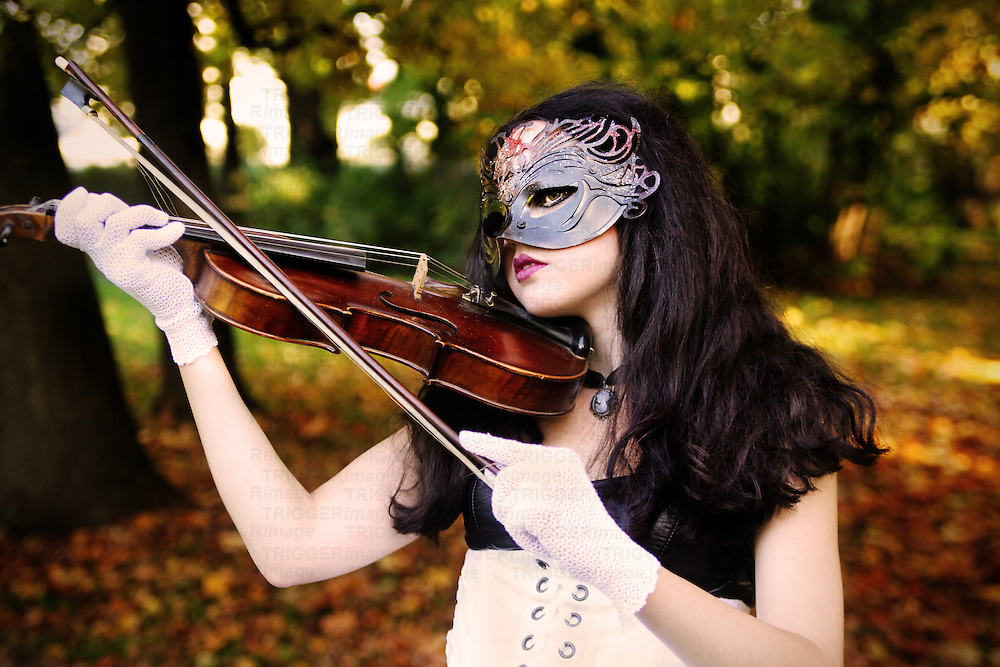 A girl with long black hair and a mask on her face playing the violin in an autumn setting.