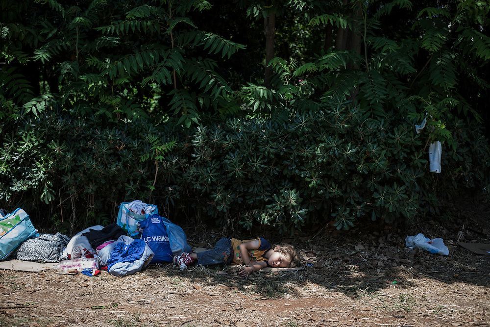 Greece, Athens, July 25th 2015 - A child is slipping on the ground next to its family belongings at Pedion tou Areos park, where hundreds of migrants and refugees mostly from Afghanistan have build a temporary camp, after they arrived in Athens from the Greek islands wishing to continue their journey to central Europe.