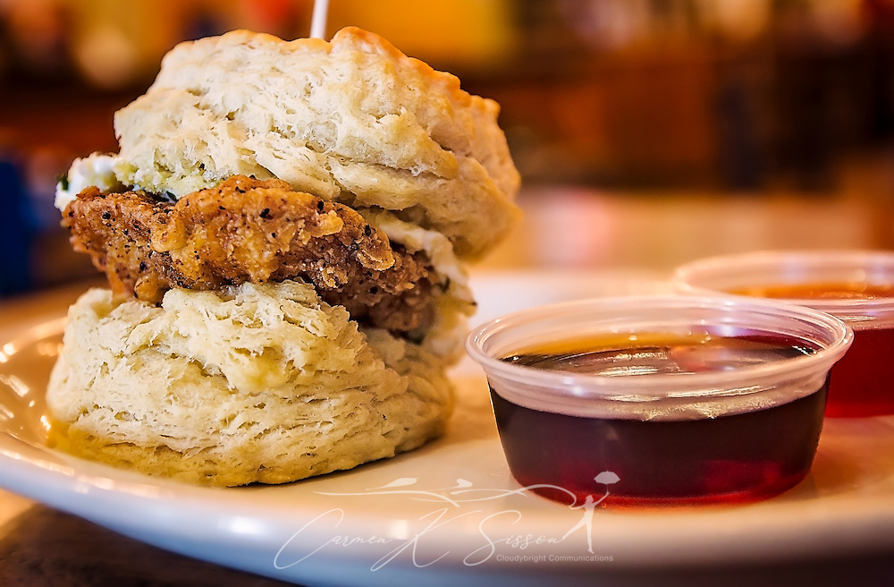 "The Loaded Goat biscuit, which features a fried chicken breast and fried goat cheese medallion, is served with maple syrup and pepper jelly at Maple Street Biscuit Company, March 21, 2016, in St. Augustine, Florida. The restaurant specializes in gourmet biscuit sandwiches and other breakfast fare. It is particularly known for ""The Five,"" which is a biscuit topped with a fried chicken breast, pecan wood-smoked bacon, cheddar cheese, and sausage gravy. (Photo by Carmen K. Sisson/Cloudybright)"