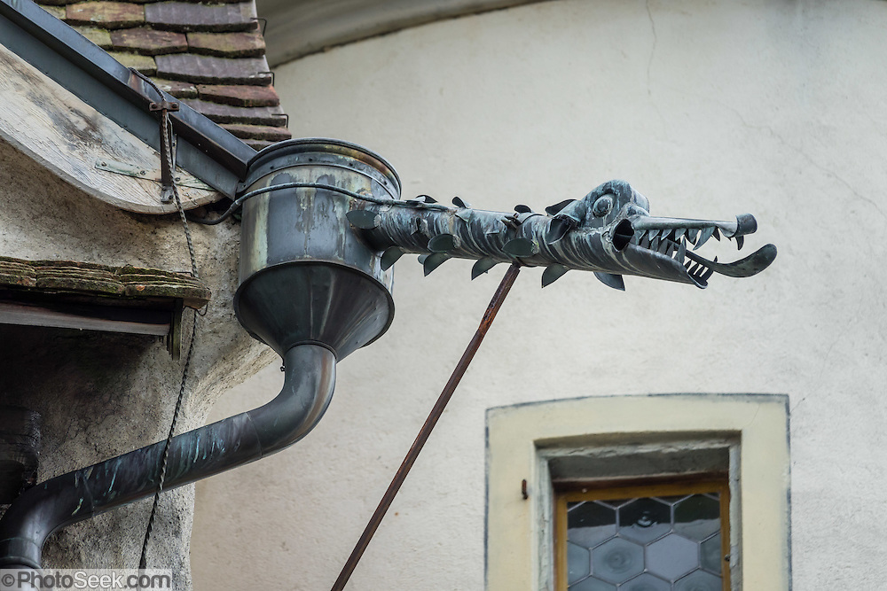 Dragon gargoyle in rain gutter downspout, Appenzell village, Switzerland, Europe. The legend of St. George slaying a dragon was a brought back with the Crusaders. According to legend, St. George (who may have lived about AD 280-303) was a Roman soldier of Greek origin and officer in the Guard of Roman emperor Diocletian, who ordered his death for failing to recant his Christian faith. As a Christian martyr, he later became one of the most venerated saints in Christianity.