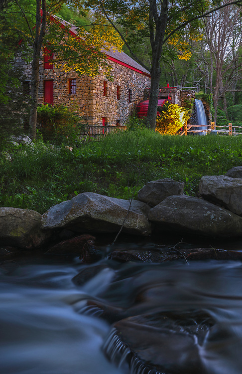 The Wayside Inn Grist Mill in Sudbury Massachusetts on a beautiful spring night in summer. A long exposure photography setting conveys the flowing water of the brook in the front and the falling waters across the Grist Mill.<br />