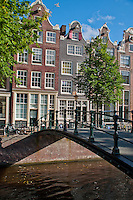 Amsterdam, Holland. Bridge over a canal with traditional Dutch buildings lining the street.
