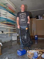 © Licensed to London News Pictures. 07/09/2013<br /> <br /> Saltburn, Cleveland, England<br /> <br /> Glenn Nary, a surfboard shaper and owner of Visionary Surfboards begins the clean up operation after his business premises were flooded following a night of heavy rain in Saltburn, Cleveland.<br /> <br /> Photo credit : Ian Forsyth/LNP