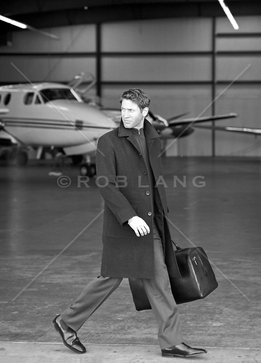 man with a suitcase at an airplane hanger