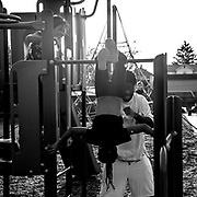 Desmond Gordon rough houses with his two daughters, Cadiera and Keionna at the playground near their home.