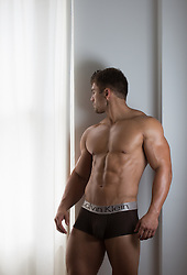 muscular All American man at home in his underwear by a window