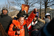 Linda Walker, of Bayshore, New York, (orange jacket) celebrates as Barack Obama is sworn in as president of the United States.