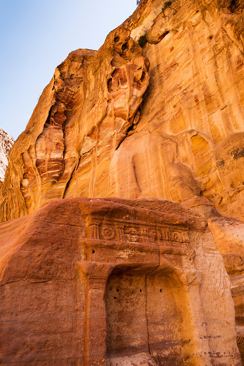 Jordan, Petra, Eroded sandstone cliffs above carved stone entrance at ancient ruins