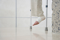Human foot of person on crutches low section