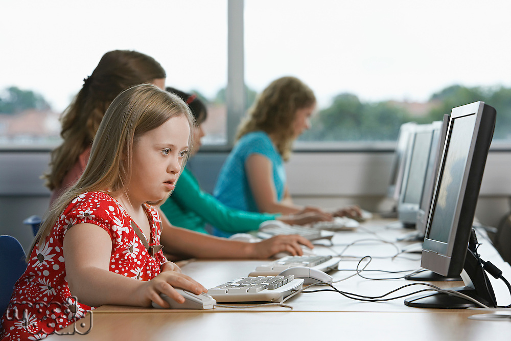 Girl (10-12) with Down syndrome using computer in computer lab children in background