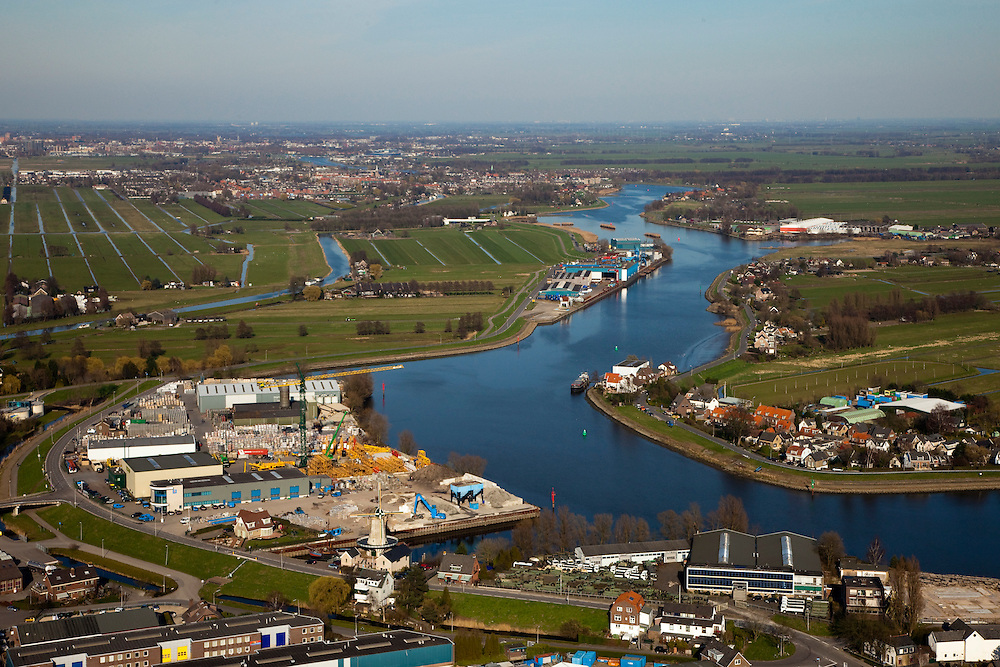Nederland, Zuid-Holland, Hollandsche IJssel, 20-03-2009; Hollandse IJssel bij buurtschap Kortenoord, ter hoogte van Nieuwerkerk aan den IJssel, Gouda aan de horizon.  De Groendijk  dreigde het tijdens de watersnood van 1953 te  begeven waardoor een groot deel van het laag gelegen en dicht bevolkte westen van Nederland ondergelopen zouden zijn. Klein industriegebied met molen Windlust..During the flood onf 1953, the dike was in a very bad shape and as a consequence the low-lying and densely populated west of the Netherlands was almost flooded..Upsteam storm surge bariers now protect this part of the country. Small industrial area with mill Windlust. .Swart collectie, luchtfoto (toeslag); Swart Collection, aerial photo (additional fee required).foto Siebe Swart / photo Siebe Swart
