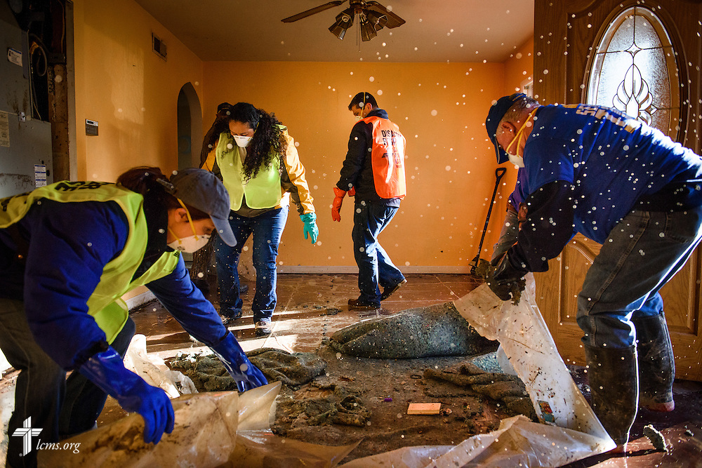 (L-R) Erica Schwan and Mireya Johnson of LCMS Communications, along with the Rev. Ross Johnson, director of LCMS Disaster Response, work with fellow volunteers from the International Center of The Lutheran Church–Missouri Synod, New Beginnings Lutheran Church in Pacific, Mo., and Missouri representatives of the Southern Baptist Convention Disaster Relief at a flooded home in Fenton on Thursday, Jan. 14, 2016. LCMS Communications/Erik M. Lunsford