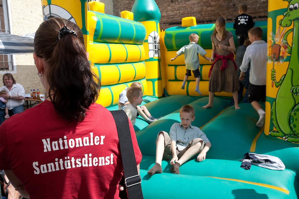 Germany - Deutschland - 1. MAI in BERLIN: Zur NPD-Kundgebung auf dem Gelände der Partei-Bundeszentrale in Berlin-Köpenick versammelten sich etwa 200 Nationalisten und Rechtsextreme.; HIER: auf dem Hof der Parteizentrale, Hüpfburg für Kinder und eine Frau des Nationalen Sanitätsdiensts....BERLIN, MAY 1: 200 Neofascists and supporters of the extrem right wing party NPD made a meeting in the party headquarter in Berlin Koepenick; 01.05.2009