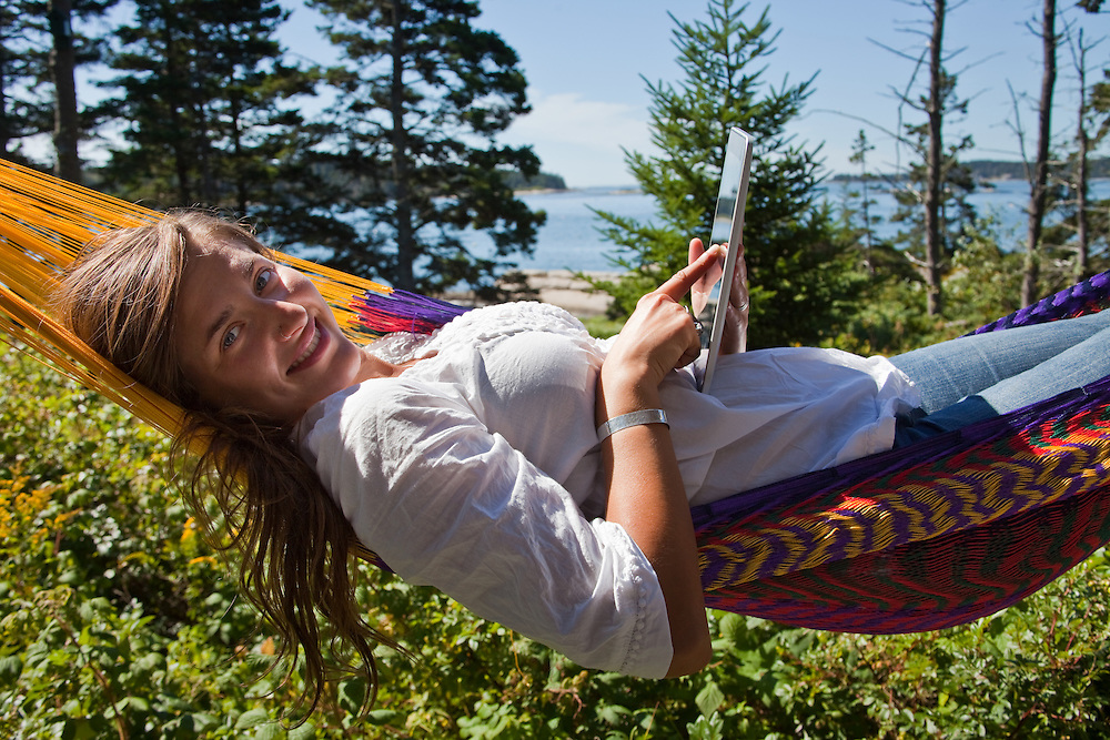 Woman smiling toward camera, lying in hammock and using a computer tablet