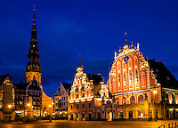 """RIGA, LATVIA - CIRCA MAY 2014: Night view of the Town Square Hall  with """"The House of Blackheads"""" and St. Peter's Church in old town Riga at night."""