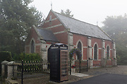 A renovated Northumbrian village chapel converted into a home with a brown-painted phone box, on 26th September 2017, in Eshott, Northumberland, England.