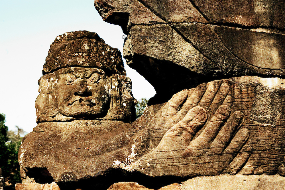 Angkor Thom : Naga balustrade on the entrance causeway over the moat.  Detail of first figure holding the naga's head.  Hand and foot discernible in foreground, in front of ferocious looking face.