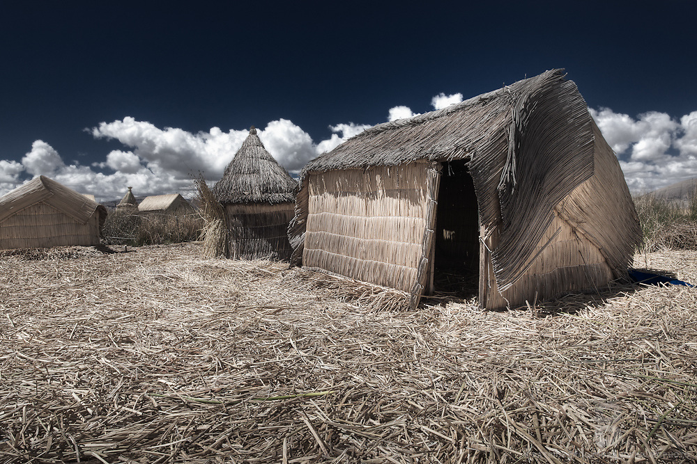 The artificial floating islands made of reeds that surround the bay of Puno on Lake Titicaca atract tons of tourists everyday and has now become the main source of income for the indigenous Uros people. Shown here is a huts and the circular shaped reed hut is the kitchen for Uros people.