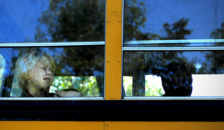 BALTIMORE, MD -- 9/18/08 -- MD CO ONLINE 19 SMITH -- Tommy Wesselhoff, 10, presses his face against the window of the school bus as he waves bye to his mother and brother Danny whom will stay at home for online schooling Tuesday morning. Tommy and Danny Wesselhoff are two of about 100 students who were enrolled in Baltimore County's virtual school instruction program last year, which continues to go unfunded this year. Danny continues on in the Connections Academy, but via a parent pay program, while Tommy heads to his zoned elementary school each morning. Patrick Smith [Sun Photographer] #8885 MANDATORY CREDIT:  Baltimore Examiner and Washington Examiner OUT