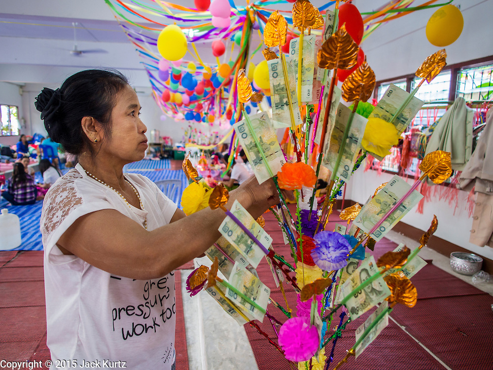 """04 APRIL 2015 - CHIANG MAI, CHIANG MAI, THAILAND: A woman donates money to a boy being ordained at the Poi Sang Long Festival in Chiang Mai. The Poi Sang Long Festival (also called Poy Sang Long) is an ordination ceremony for Tai (also and commonly called Shan, though they prefer Tai) boys in the Shan State of Myanmar (Burma) and in Shan communities in western Thailand. Most Tai boys go into the monastery as novice monks at some point between the ages of seven and fourteen. This year seven boys were ordained at the Poi Sang Long ceremony at Wat Pa Pao in Chiang Mai. Poy Song Long is Tai (Shan) for """"Festival of the Jewel (or Crystal) Sons.      PHOTO BY JACK KURTZ"""