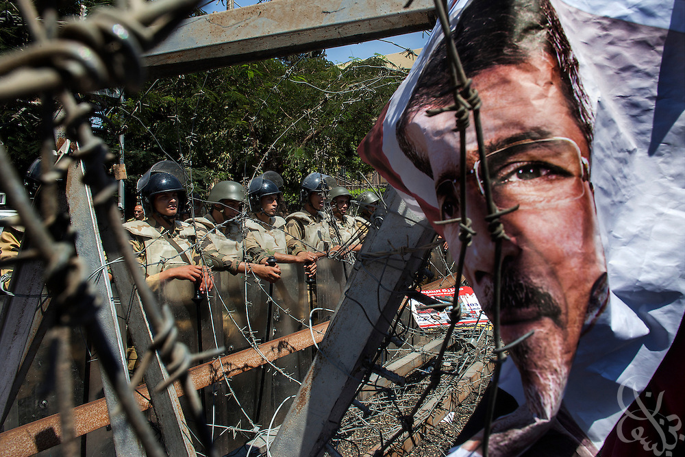 A Pro-Morsi sign sign posted to a barbed wire barricade is seen in front of Egyptian soldiers standing guard behind during a protest march by female Muslim Brotherhood members and other supporters of deposed Egyptian president Mohamed Morsi near the Defense Ministry building in the Abbasiya district of Cairo Friday July 30, 2013.  The Muslim Brotherhood has maintained a steady wave of protests and sit-ins for a month since Morsi was deposed by the Egyptian military and replaced by an interim government, and vow to continue until he is reinstated.