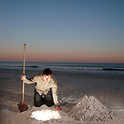 Wrightsville Beach, North Carolina - March 18: Davis McCeiver leans over a glowing hole on the beach at sunset in Wrightsville Beach, North Carolina, on March 18, 2007.