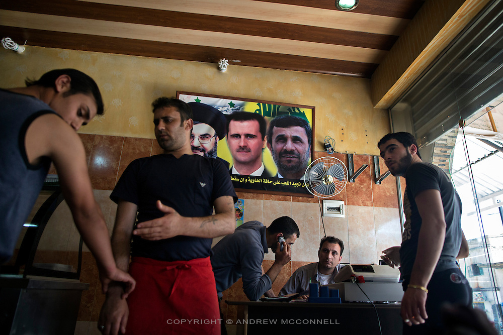 A poster on the wall of a restaurant shows Hezbollah leader Hassan Nasrallah, Syrian President Bashar al-Assad, and Iranian President Mahmoud Ahmadinejad, in Hermel, Lebanon. The northern town of Hermel is a Hezbollah stronghold and lies close to Syrian border, as such it has witnessed repeated rockets attacks from rebels inside Syria angered by Hezbollah support for the Syrian regime.
