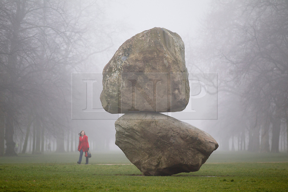 © Licensed to London News Pictures. 08/03/2013. London, UK. A visitor to Hyde Park view a giant boulder sculpture entitled 'Rock on Top of Another Rock' by Swiss artists Fischli/Weiss in outside the Serpentine Gallery in London, today (08/03/2013). The installation, which was unveiled today, is the first sculpture by the artists - Peter Fischli (b. 1952) and David Weiss (1946-2012) - to be presented in the UK.  Photo credit: Matt Cetti-Roberts/LNP