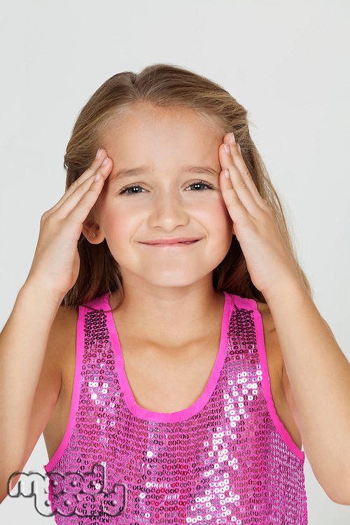 Portrait of young confused girl with hands on head against gray background