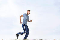 Full length of sporty man jogging against sky
