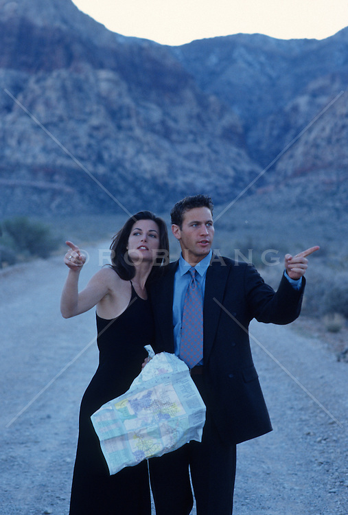 Couple dressed up in the Nevada desert with a road map deciding which way to go