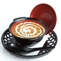 Bowl of sweet potato soup over white background