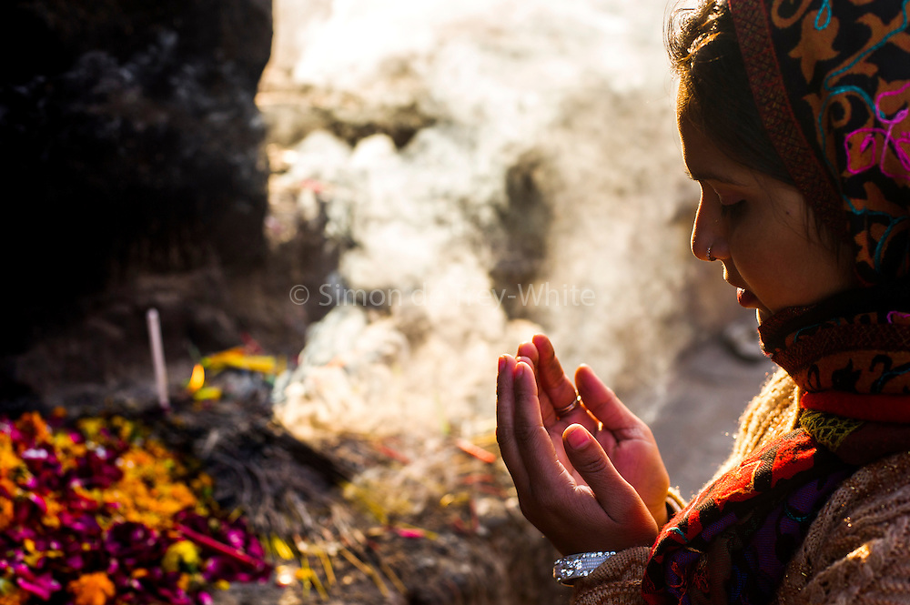 29th January 2015, New Delhi, India. A woman prays to Djinns in the ruins of Feroz Shah Kotla in New Delhi, India on the 29th January 2015<br /> <br /> PHOTOGRAPH BY AND COPYRIGHT OF SIMON DE TREY-WHITE a photographer in delhi. + 91 98103 99809. Email:simon@simondetreywhite.com<br /> <br /> People have been coming to Firoz Shah Kotla to leave written notes and offerings for Djinns in the hopes of getting wishes granted since the late 1970's. Jinn, jann or djinn are supernatural creatures in Islamic mythology as well as pre-Islamic Arabian mythology. They are mentioned frequently in the Quran  and other Islamic texts and inhabit an unseen world called Djinnestan. In Islamic theology jinn are said to be creatures with free will, made from smokeless fire by Allah as humans were made of clay, among other things. According to the Quran, jinn have free will, and Iblīs abused this freedom in front of Allah by refusing to bow to Adam when Allah ordered angels and jinn to do so. For disobeying Allah, Iblīs was expelled from Paradise and called &quot;Shayṭān&quot; (Satan).They are usually invisible to humans, but humans do appear clearly to jinn, as they can possess them. Like humans, jinn will also be judged on the Day of Judgment and will be sent to Paradise or Hell according to their deeds. Feroz Shah Tughlaq (r. 1351&ndash;88), the Sultan of Delhi, established the fortified city of Ferozabad in 1354, as the new capital of the Delhi Sultanate, and included in it the site of the present Feroz Shah Kotla. Kotla literally means fortress or citadel.