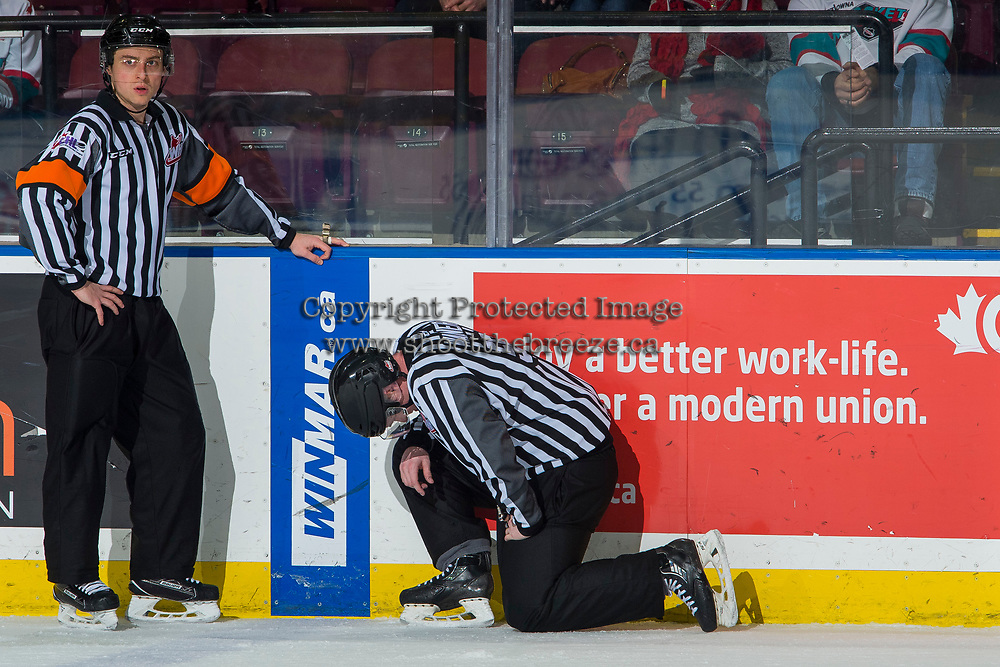 KELOWNA, CANADA - JANUARY 30:  Referee Mark Pearce stands with linesman Cody Wanner on the ice after being hit with a puck at the Kelowna Rockets against the Seattle Thunderbirds on January 30, 2019 at Prospera Place in Kelowna, British Columbia, Canada.  (Photo by Marissa Baecker/Shoot the Breeze)