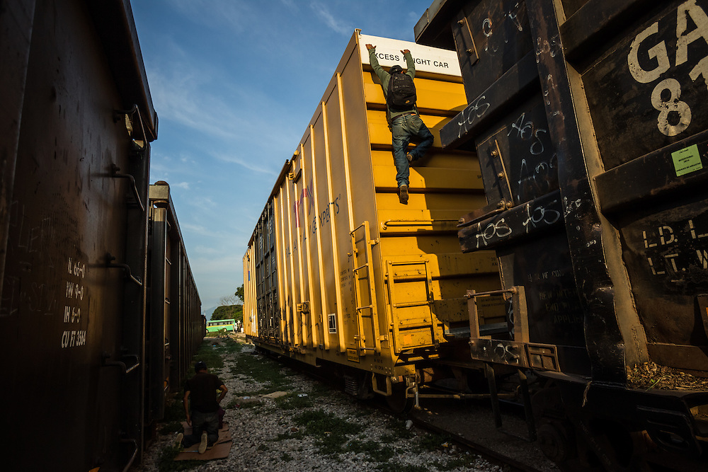 "IXTEPEC, MEXICO - JULY 7, 2014:  Geraldo Leonardo Guzman, 17, climbs down from a parked train in Ixtepec.  Guzman was born in Guatemala City, and is migrating north on the train migrants call, ""The Beast"", with hopes of making it to Arizona to work in agriculture.  He said both of his parents died and that he has no family, and that he cannot stay in Guatemala.  PHOTO: Meridith Kohut for The New York Times"