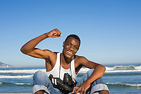 Man sitting on beach with with football boots round his neck cheering