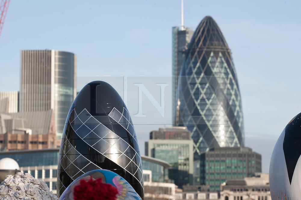 © licensed to London News Pictures. London, UK 20/02/2012. The Gherkin build is pictured with its replica egg as 30 special designed eggs are positioned together by Elephant Family and Action for Children charities for a photo opportunity in front of Tower Bridge. Photo credit: Tolga Akmen/LNP