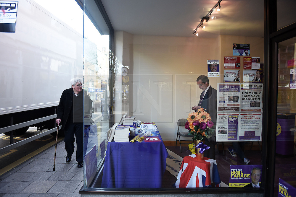 """© London News Pictures. """"Looking for Nigel"""". A body of work by photographer Mary Turner, studying UKIP leader Nigel Farage and his followers throughout the 2015 election campaign. PICTURE SHOWS - A local man looks in through the window at Nigel Farage as he fiddles on his mobile phone, in the UKIP office in Ramsgate, Kent ahead of an 'Action Day', to help the party leader in his bid to become the local MP in South Thanet, on April 12th 2015. . Photo credit: Mary Turner/LNP **PLEASE CALL TO ARRANGE FEE** **More images available on request**"""
