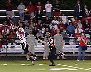 Chased by senior Ryan Sedler (85) senior Marcus Bonner (12) catches a ball near 10 yard line at the end of the first quarter as the Wayne Warriors play the Beavercreek High School Beavers at the Frank Zink Field in Beavercreek, Friday, October 7, 2011.