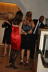 Left to right, LISA BILTON helps TARA ARCHER with her dressat the Feast of Albion a sumptious locally-sourced banquet in aid of The Soil Association held at The Guildhall, City of London on 12th March 2008.<br />