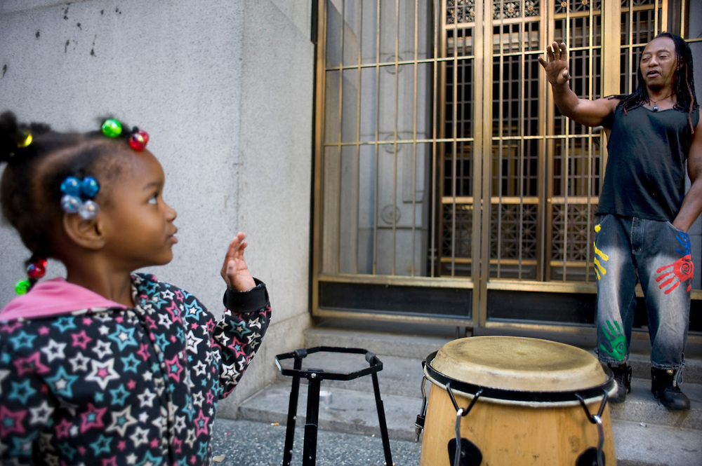 Preschooler AeNaih McCullough, age 4, from Small World 2 Early Learning & Development Center waves goodbye to drummer Price Bennett on Smithfield Street. The preschoolers take regular walks through downtown Pittsburgh.